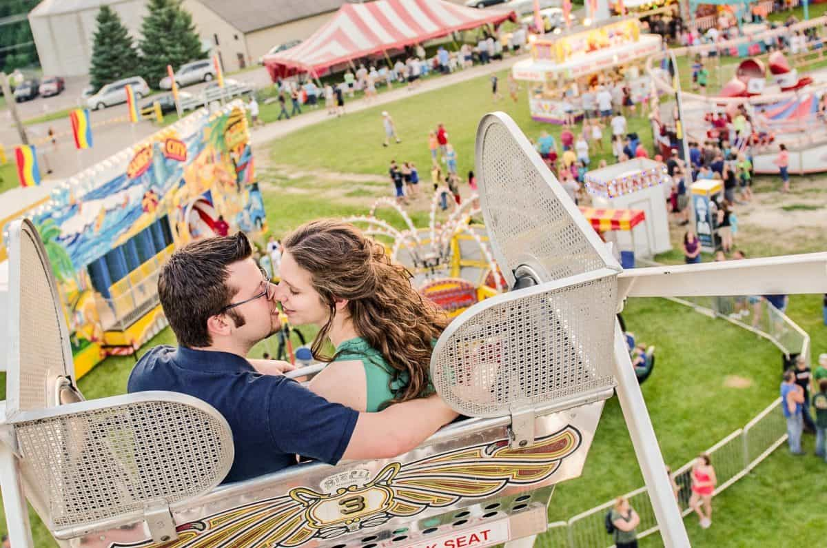 Engaged couple riding on Ferris wheel in Lodi, WI