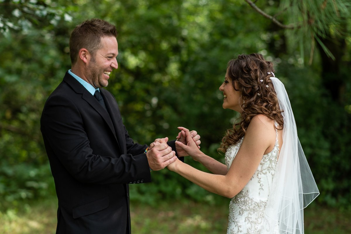 Groom holding bride's hands with a big smile