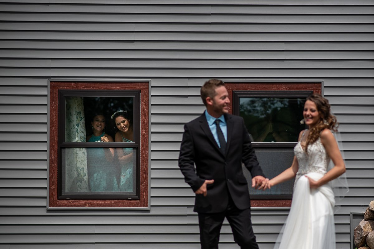 Bridesmaids peaking at couple through a window