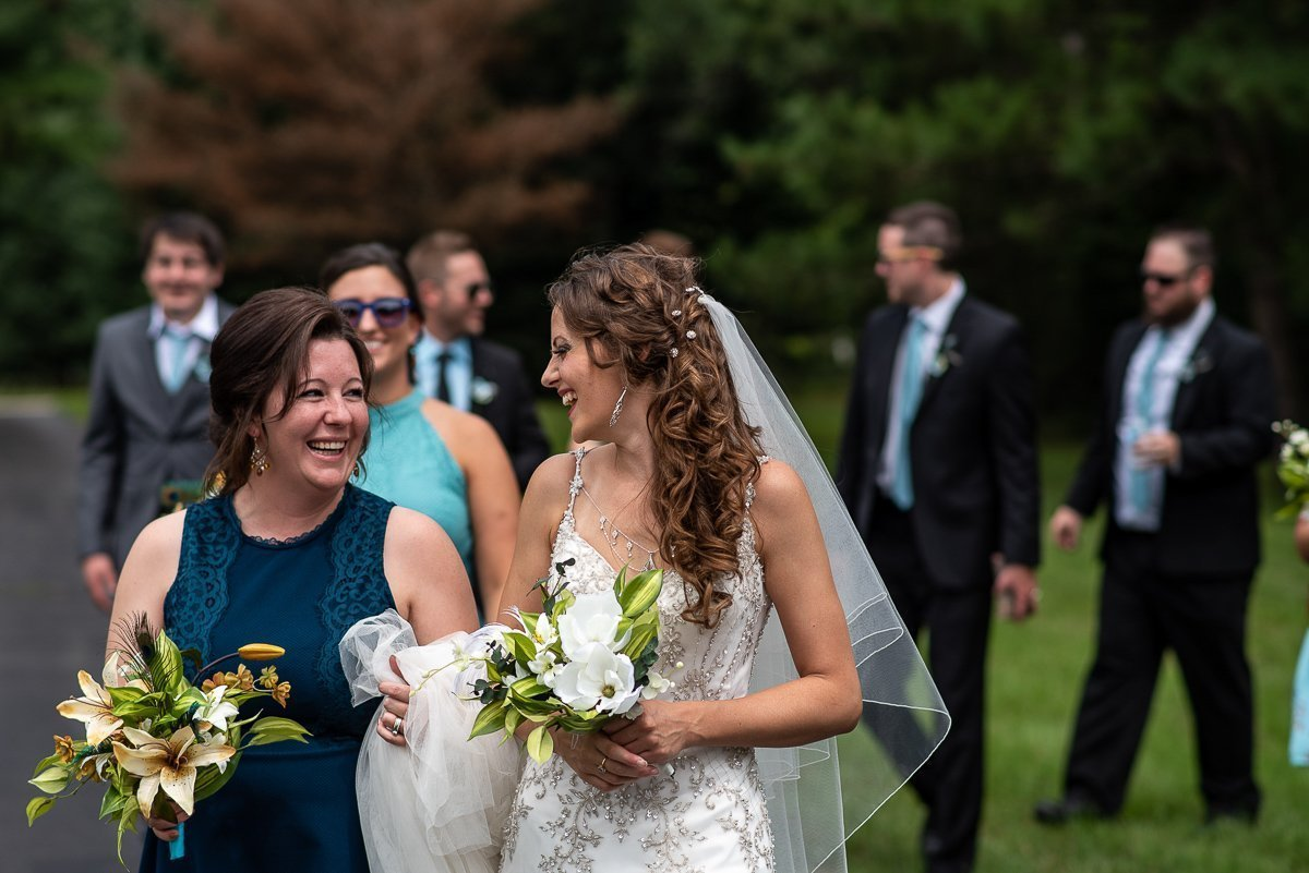Bride and bridesmaid walking together with groomsman on the background