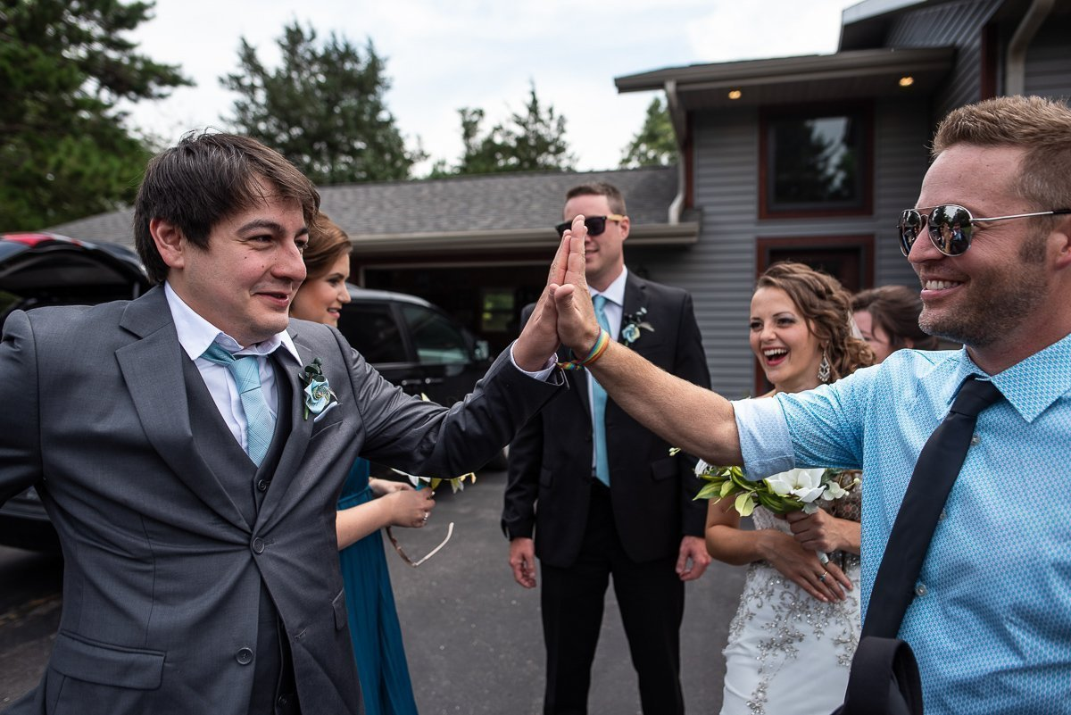 Groomsman giving a high five to groom