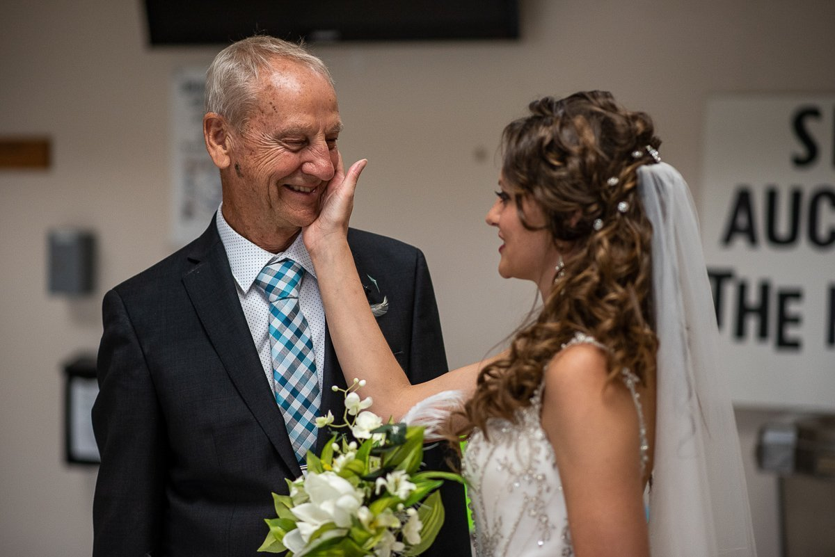 Bride touching her father's face at Saint Mary Magdalene Waupaca