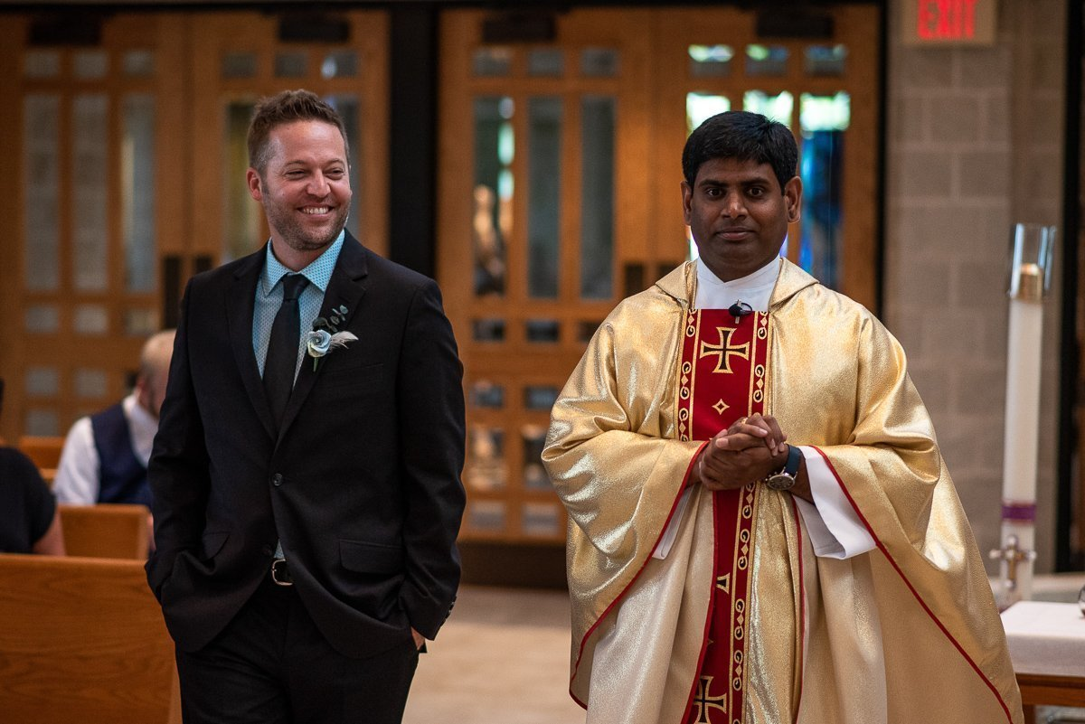 Groom walking towards the altar with priest on by side