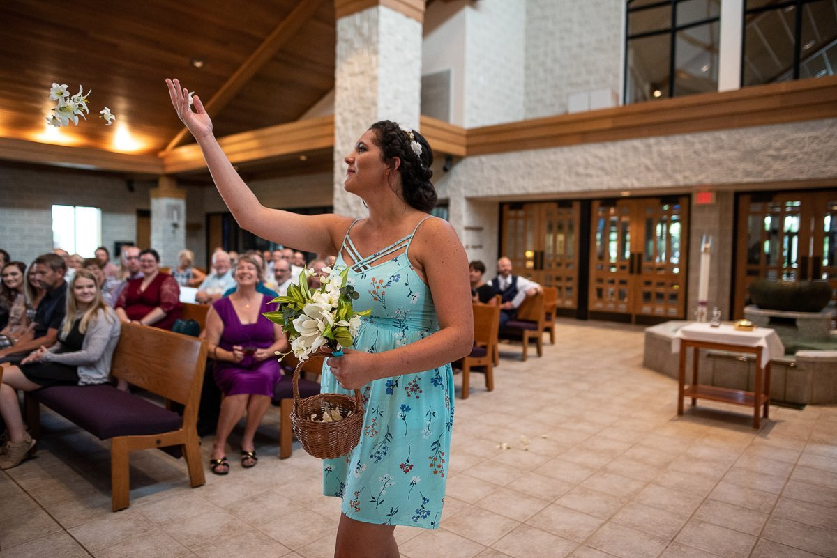 Bridesmaid throwing flowers on the air at Saint Mary Magdalene inWaupaca