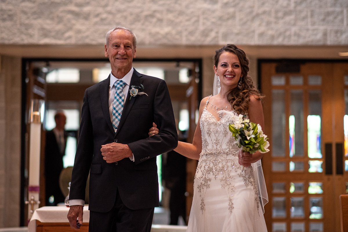 Bride and her father walking up the aisle during ceremony