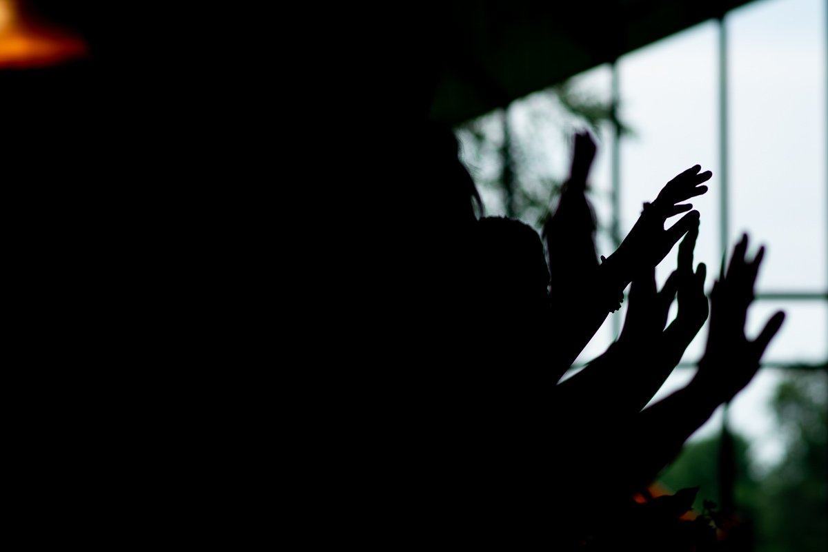 Silhouette of the bridesmaids' hands blessing the couple