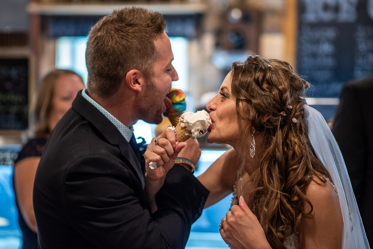 Bride and groom eating ice cream with arms crossed