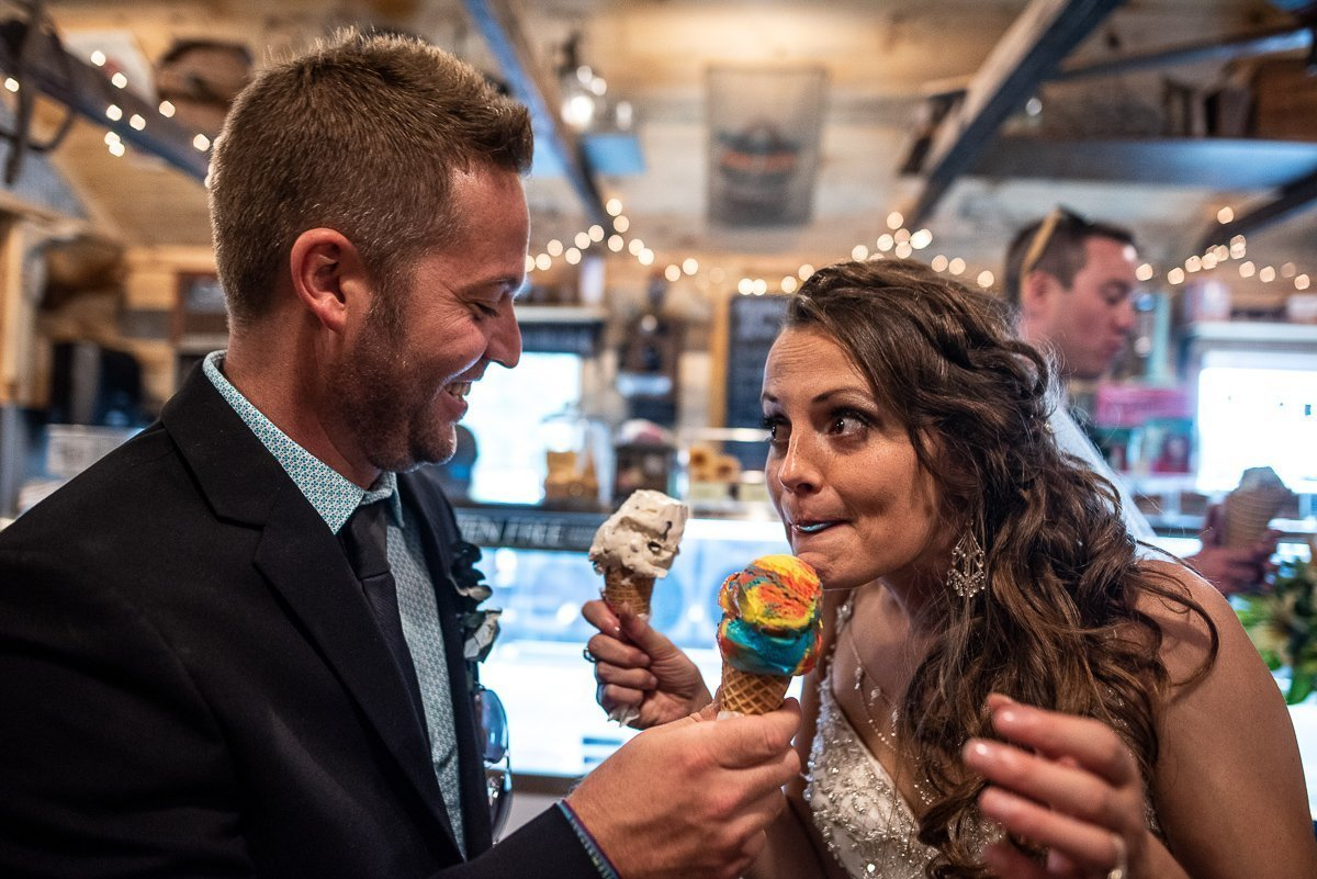 Groom holding an ice cream cone for the bride to eat