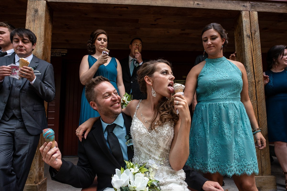 Bride eating ice cream while seating on groom's lap