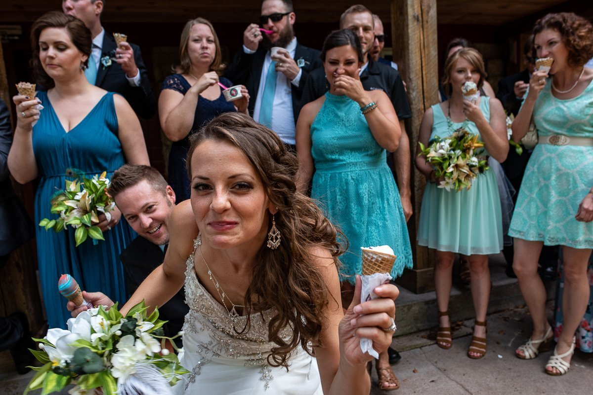 Bride eating ice cream with groom and wedding party on the background