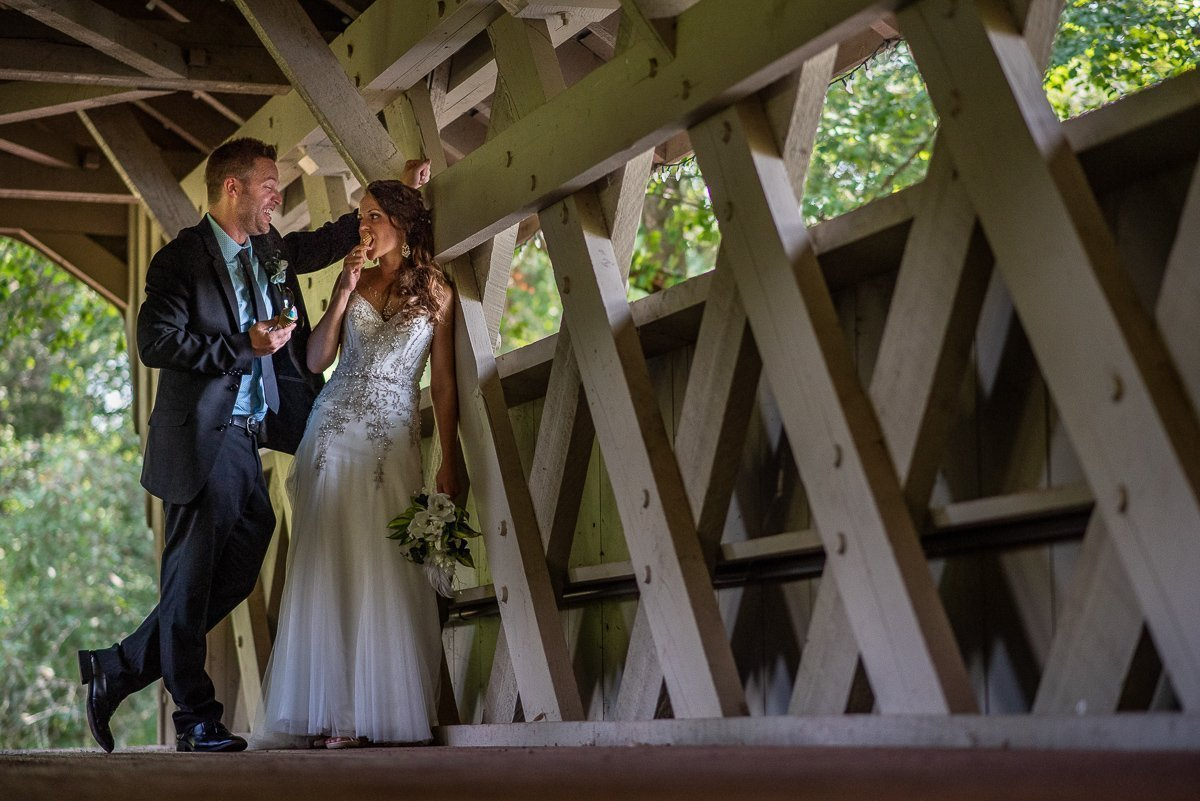 Bride and groom eating ice cream on a bridge
