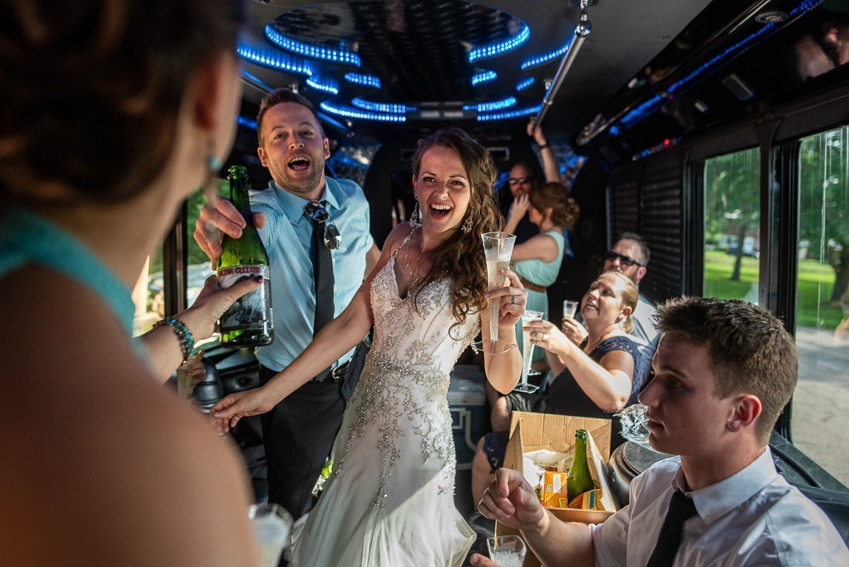 Bride and groom at the party bus drinking champaign