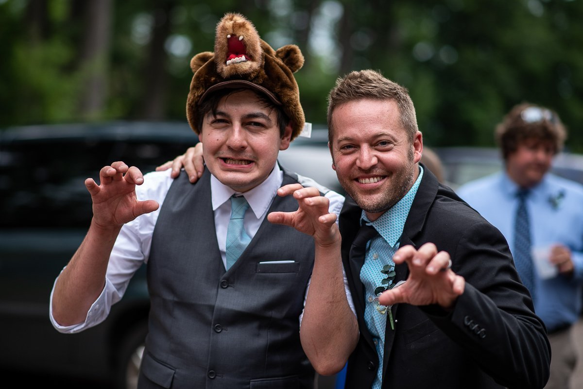 Groom and groomsman posing with bear hat