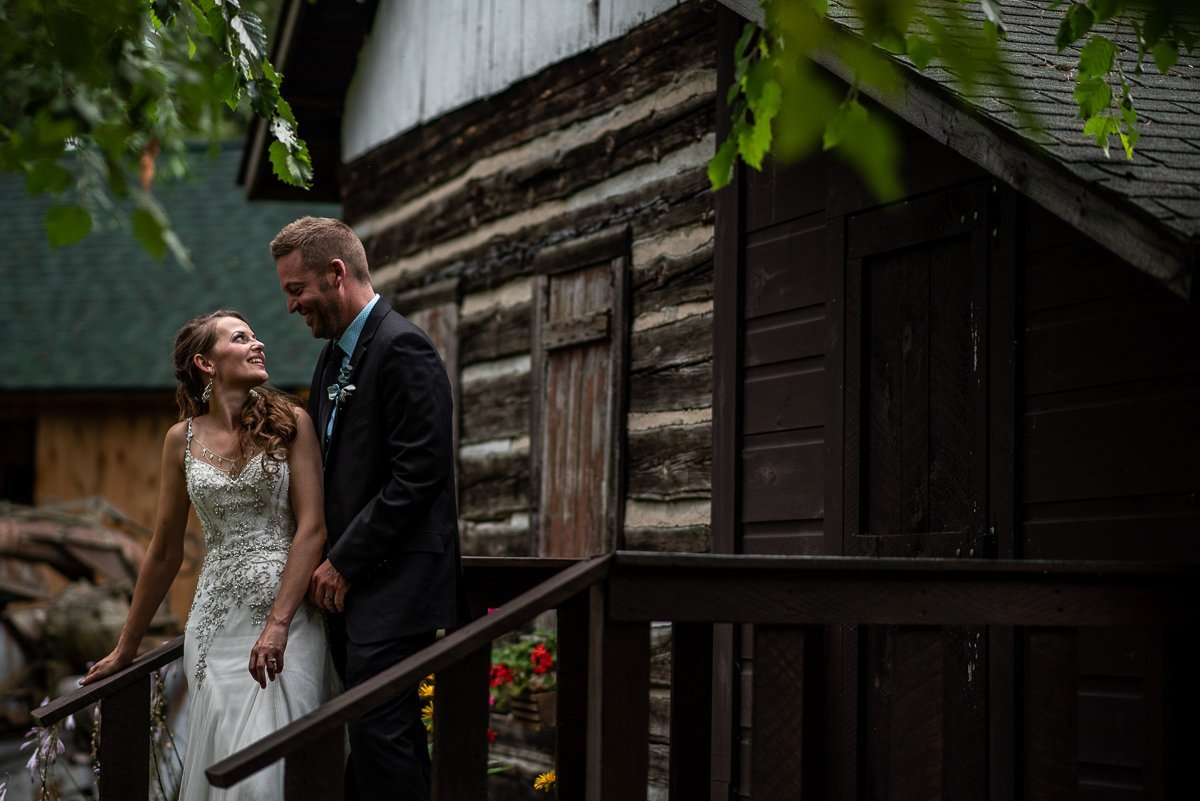 Bride and groom staring at each other with log cabin in the background