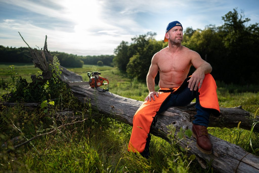 shirtless man sitting on dead tree trunk
