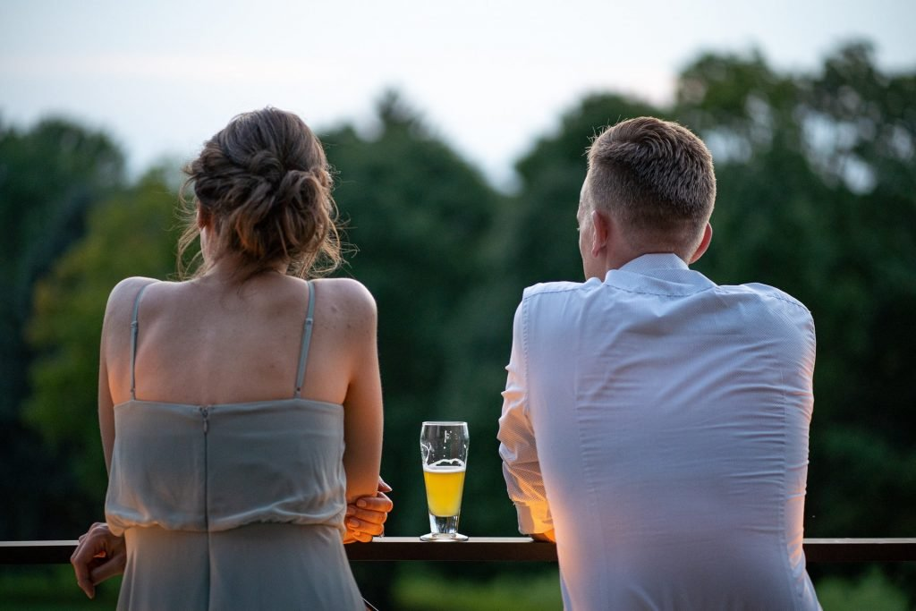 couple with a cup of beer in between them