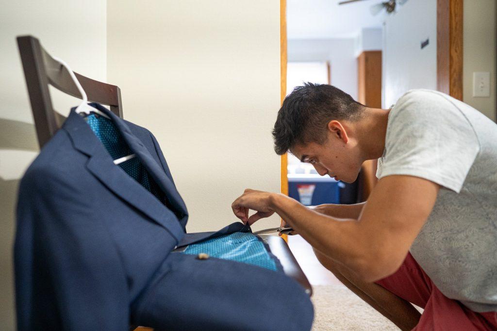 best man fixing grooms jacket
