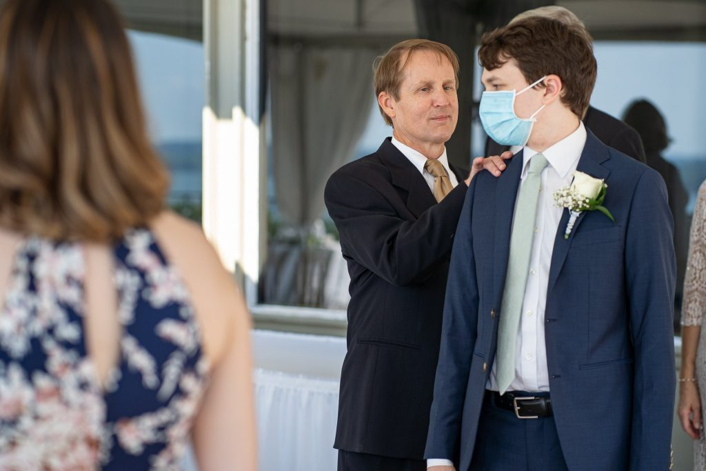father tapping grooms shoulder before wedding ceremony