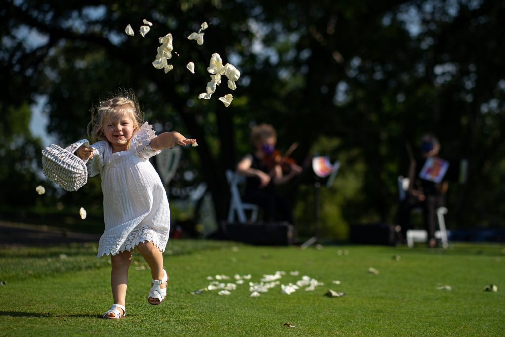 flower girl throwing white flower petals in the air