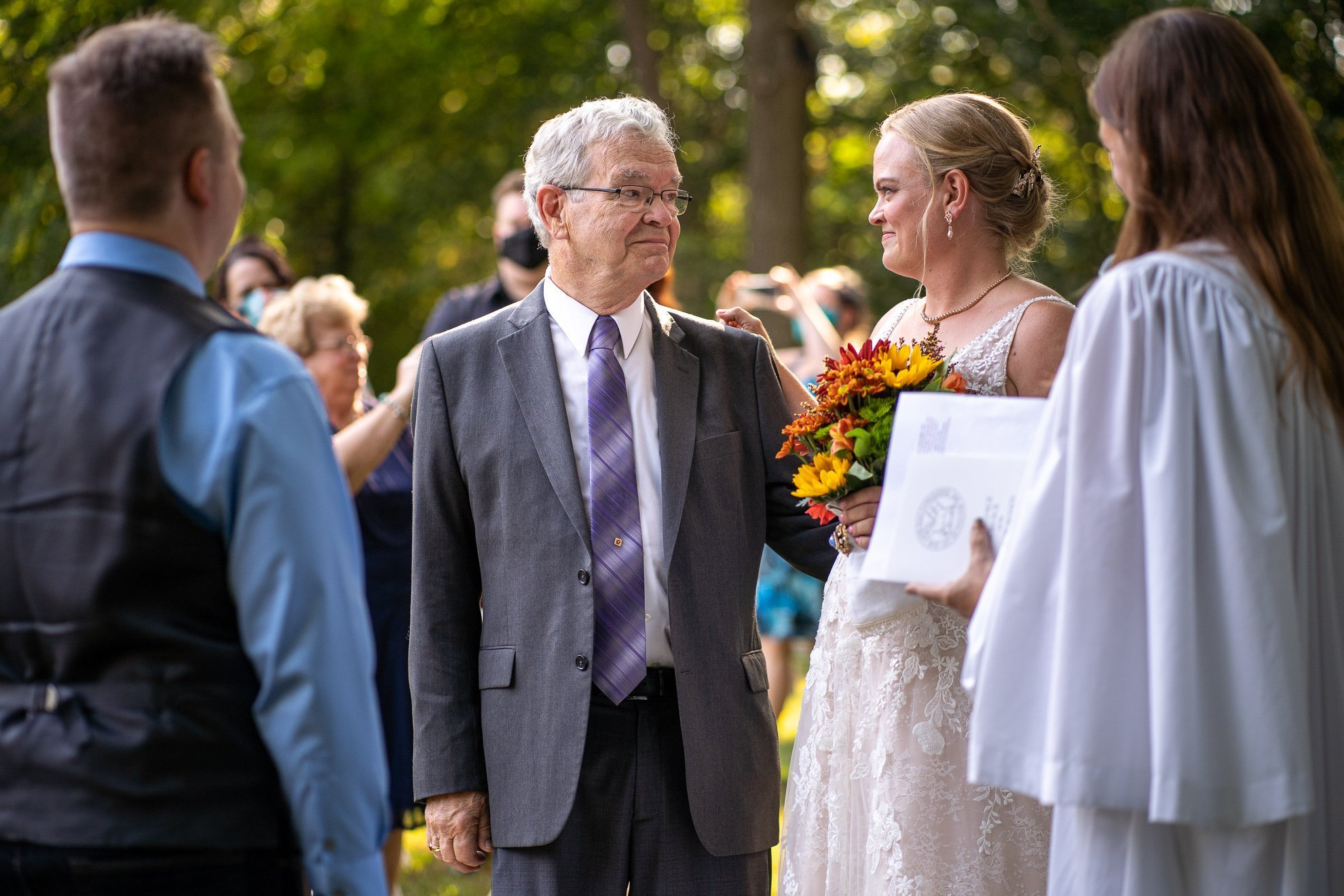 father looking at brides eyes before giving her hand