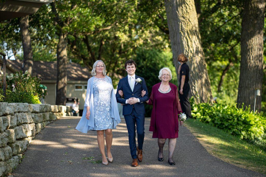 groom walking down the aisle with grandma and mom