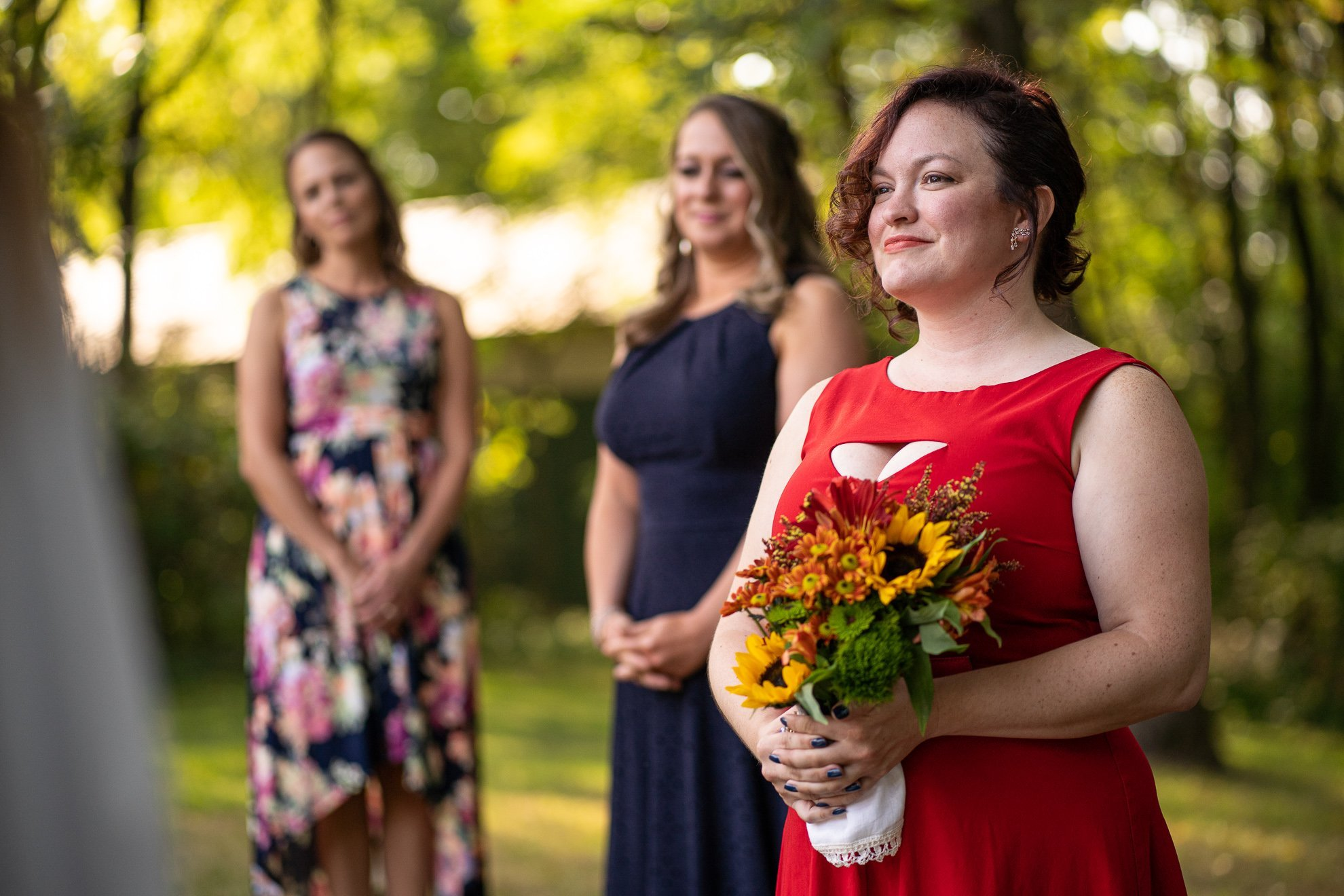 maid of honor holding flowers during wedding ceremony