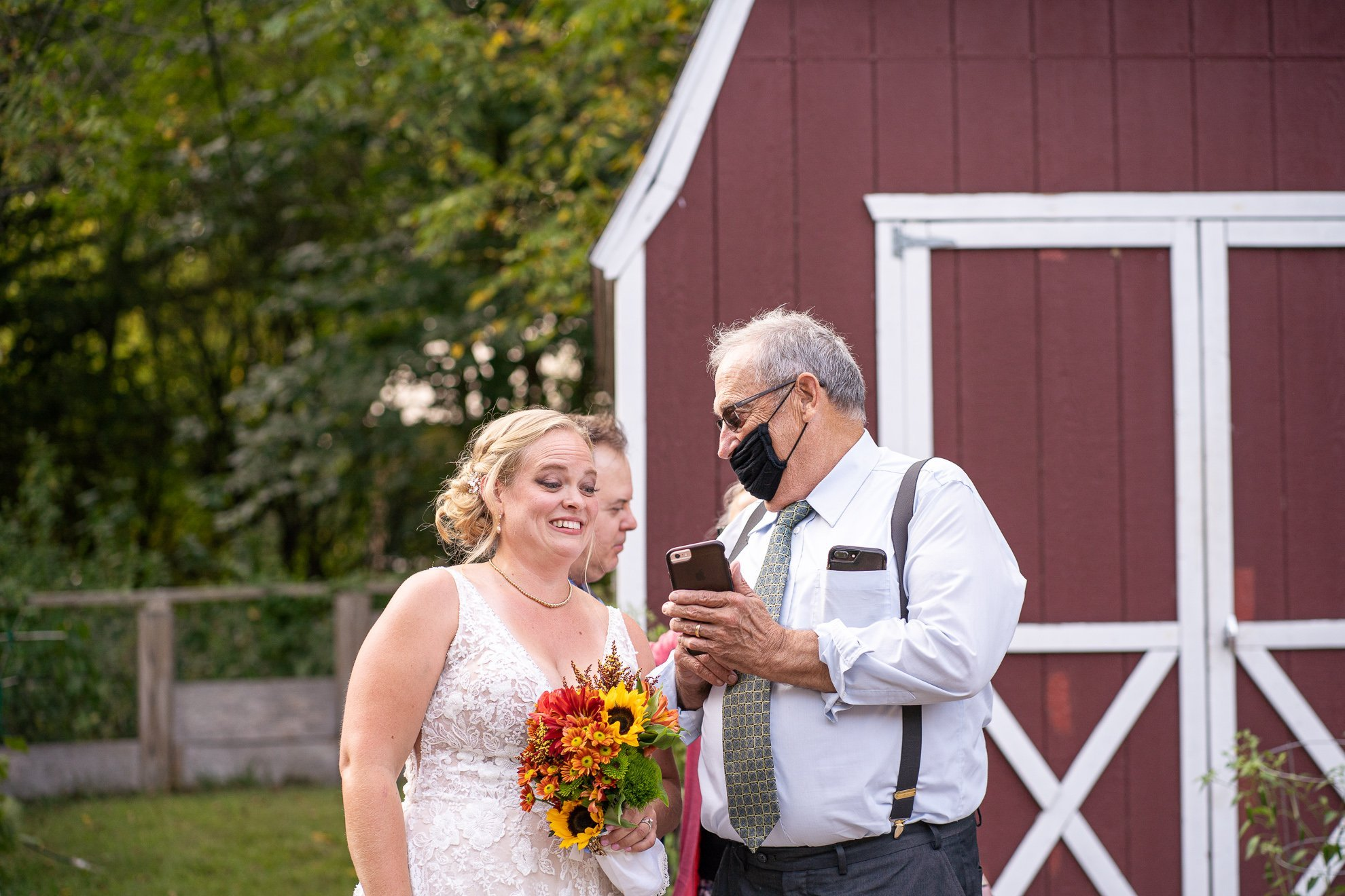 guest showing a picture on the cellphone to bride