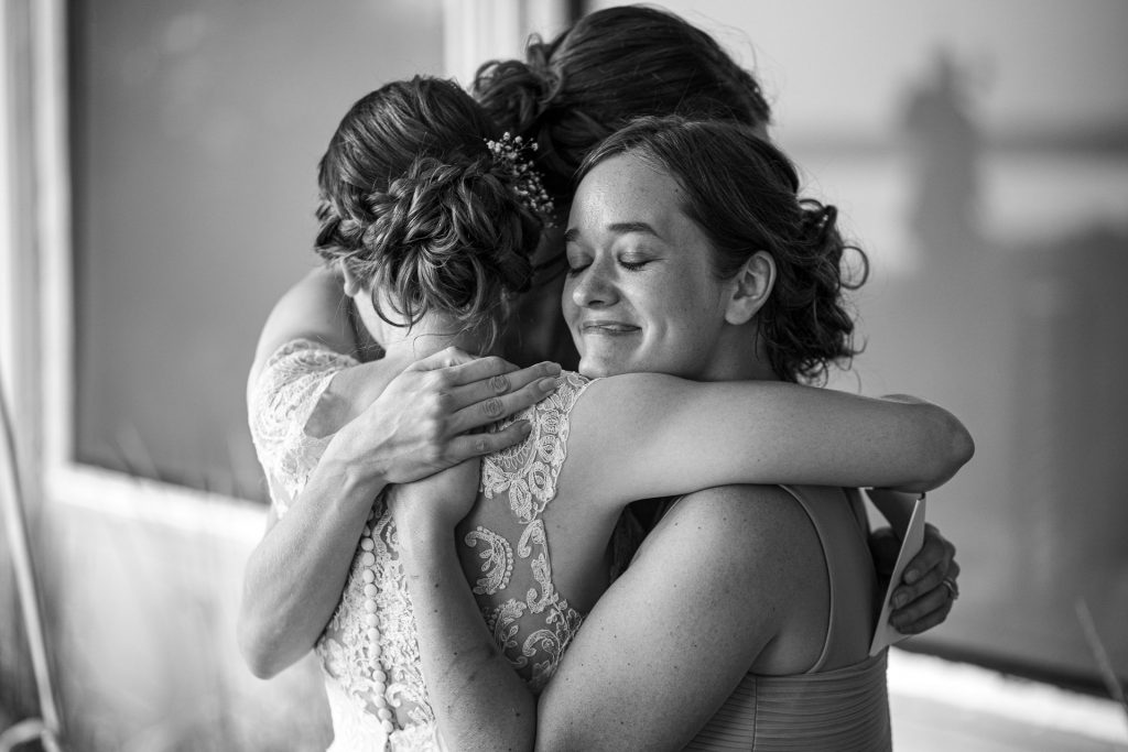 bride hugging her sisters photography