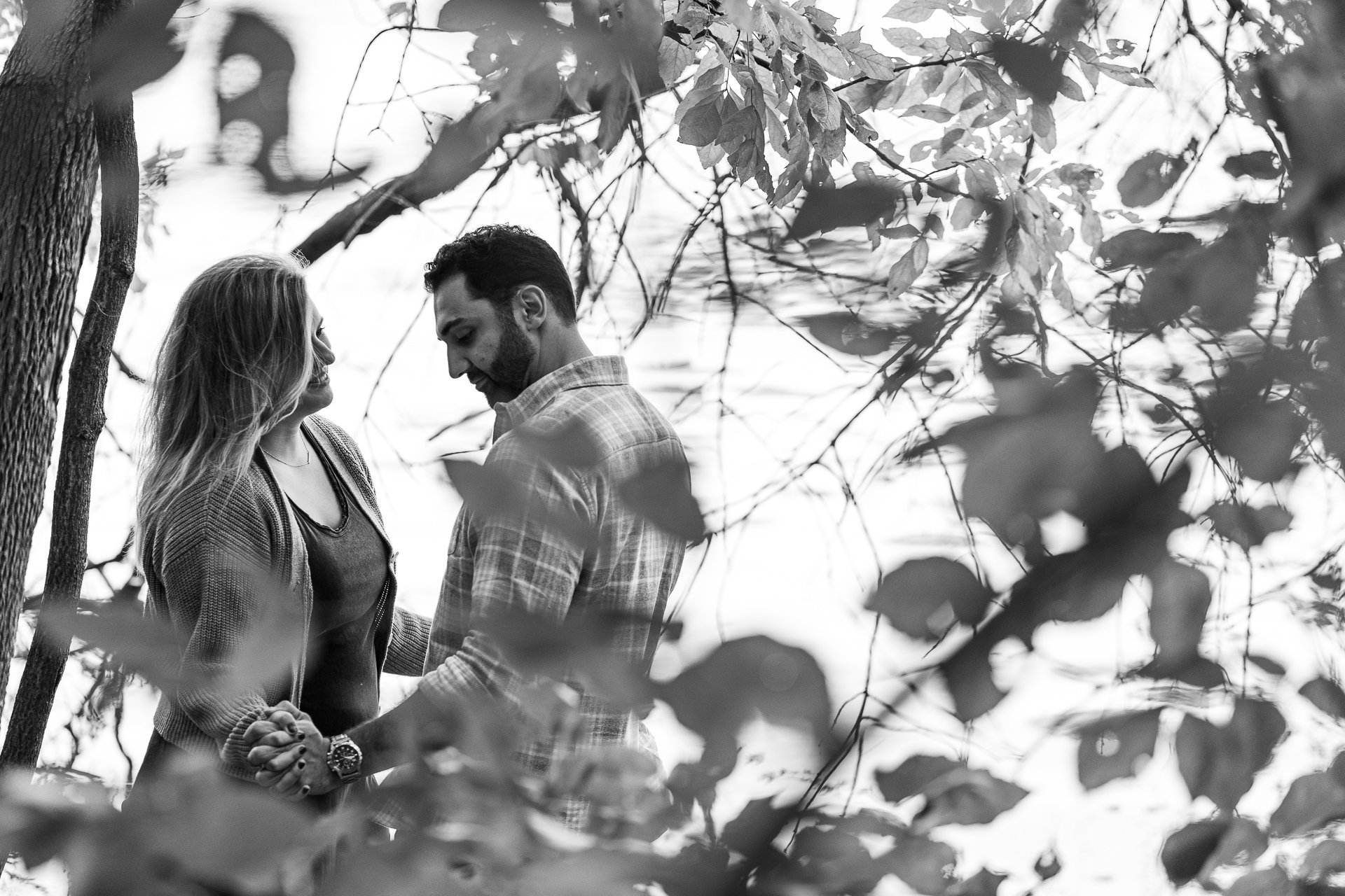 engaged couple surrounded by leaves