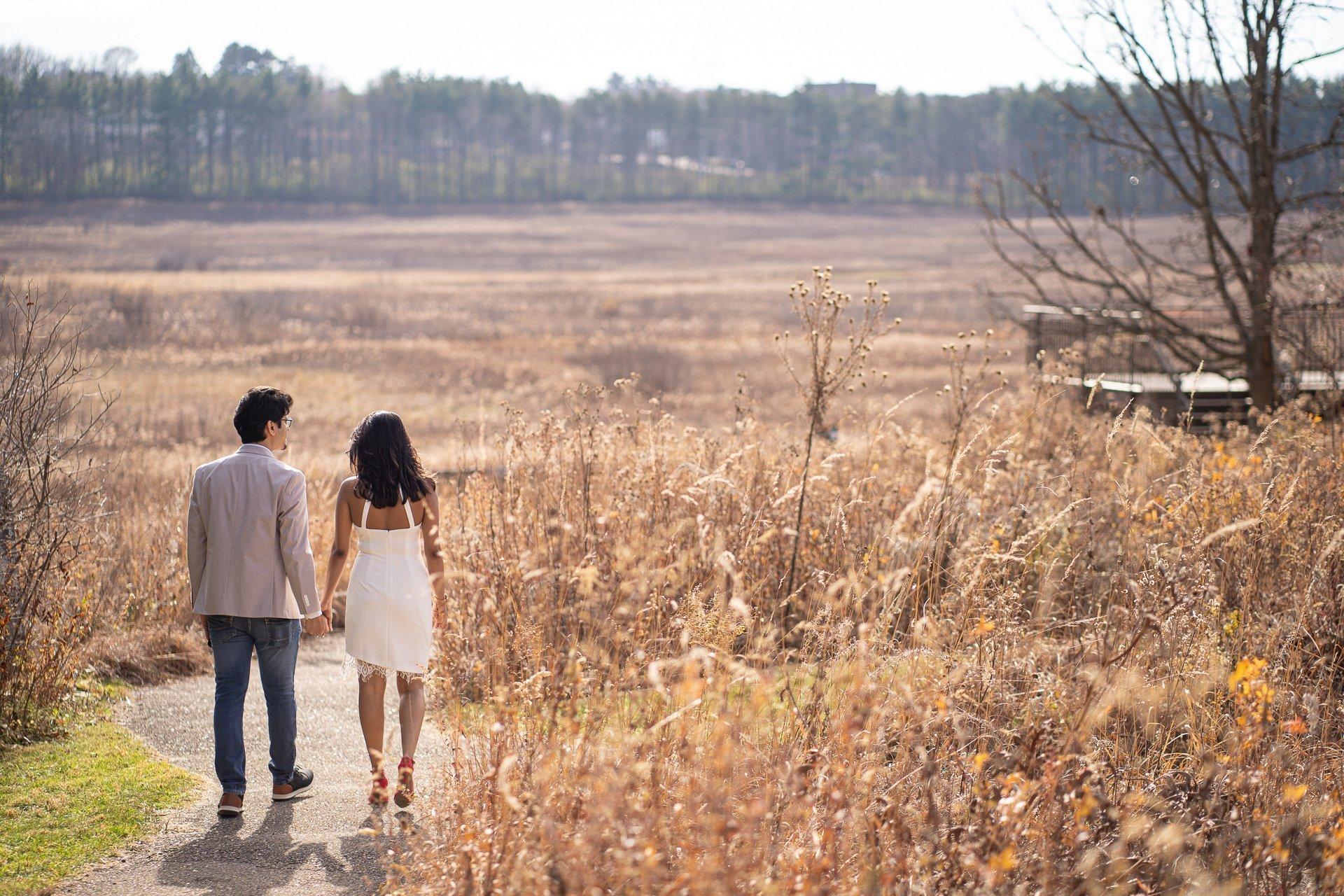 couple walking tall grass