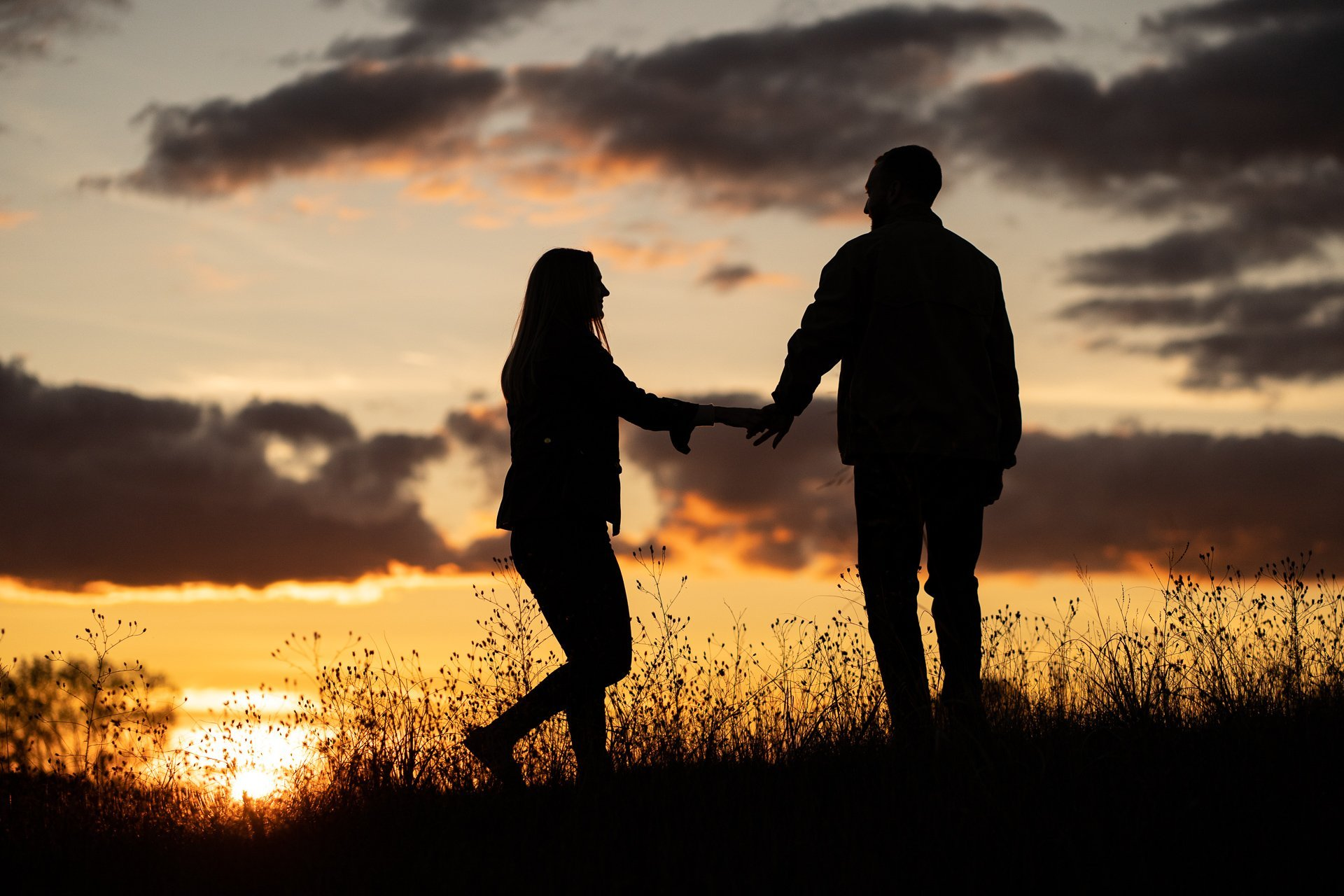 engaged couple silhouette during sunset
