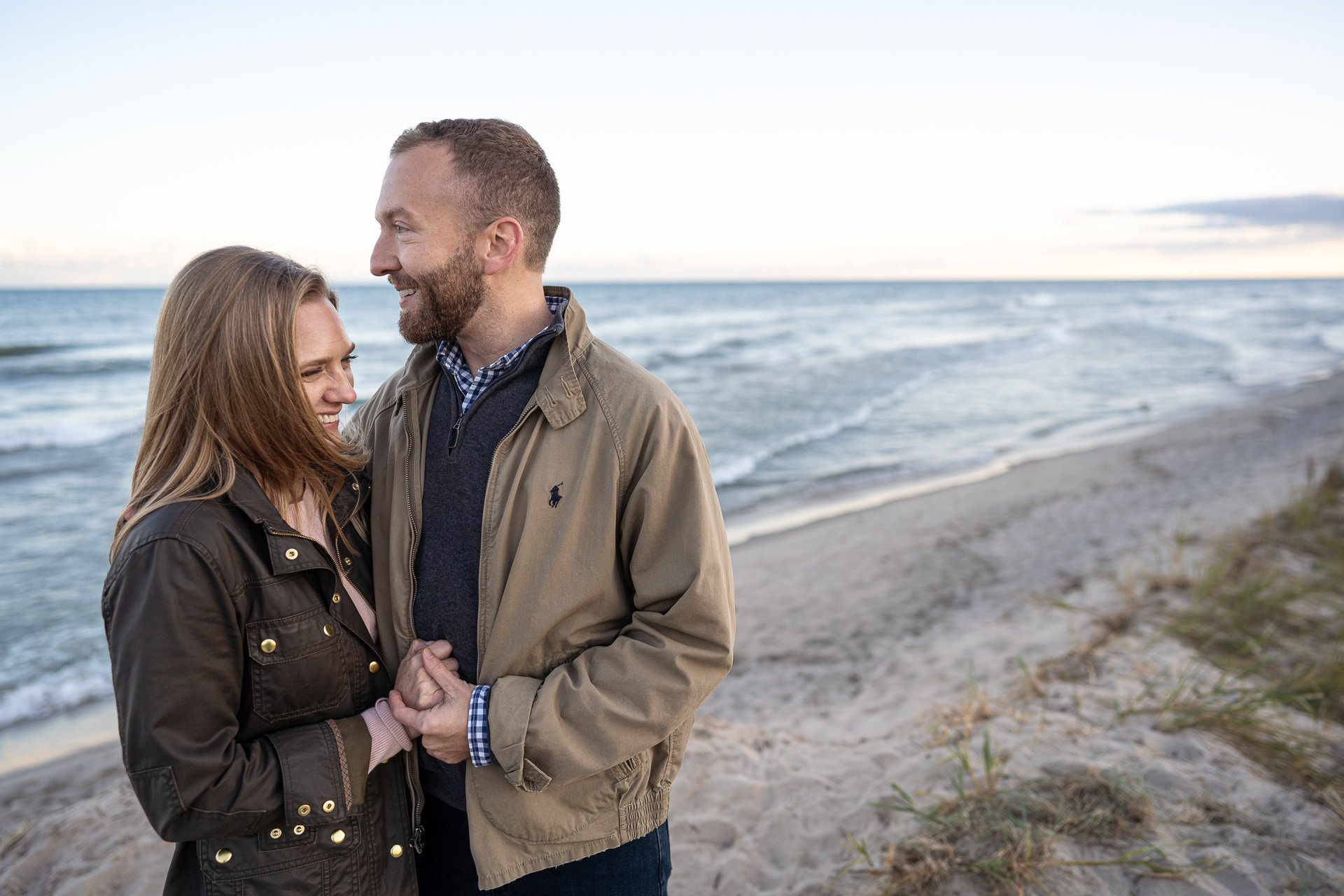 man and woman smiling by lake michigan