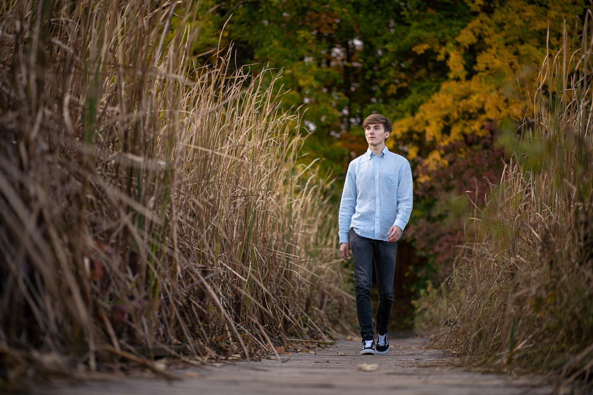 young man walking tall grass