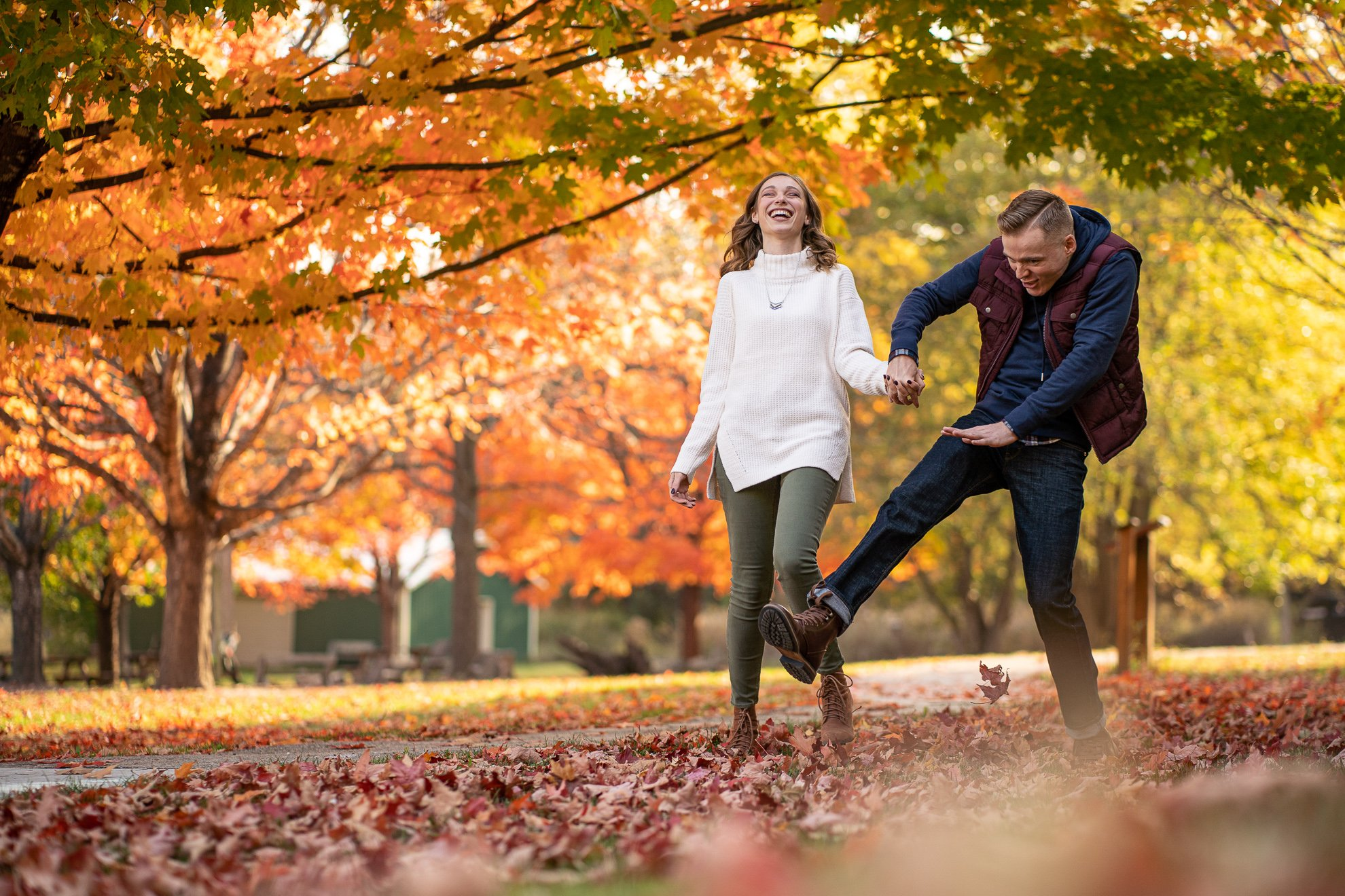 Engagement Pictures Madison WI Man Kicking Leaves