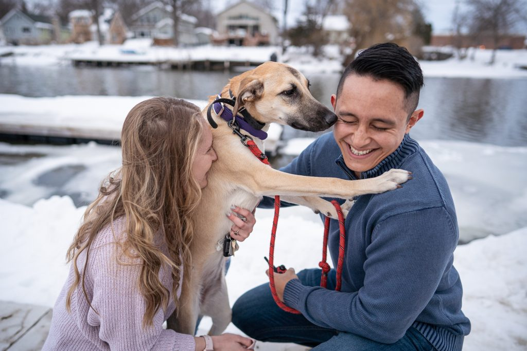 couple with dog licking man