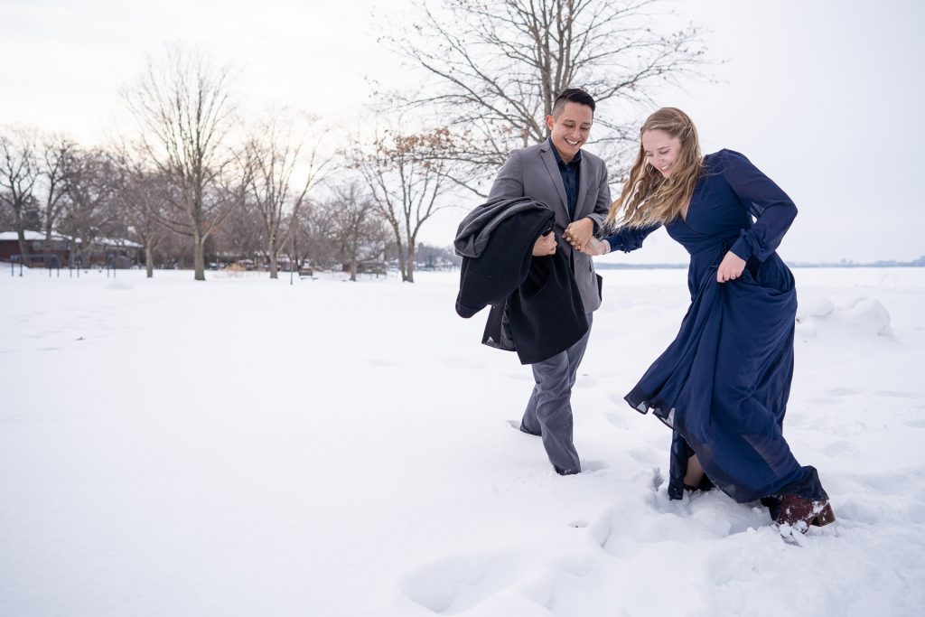 playful couple snow engagement session