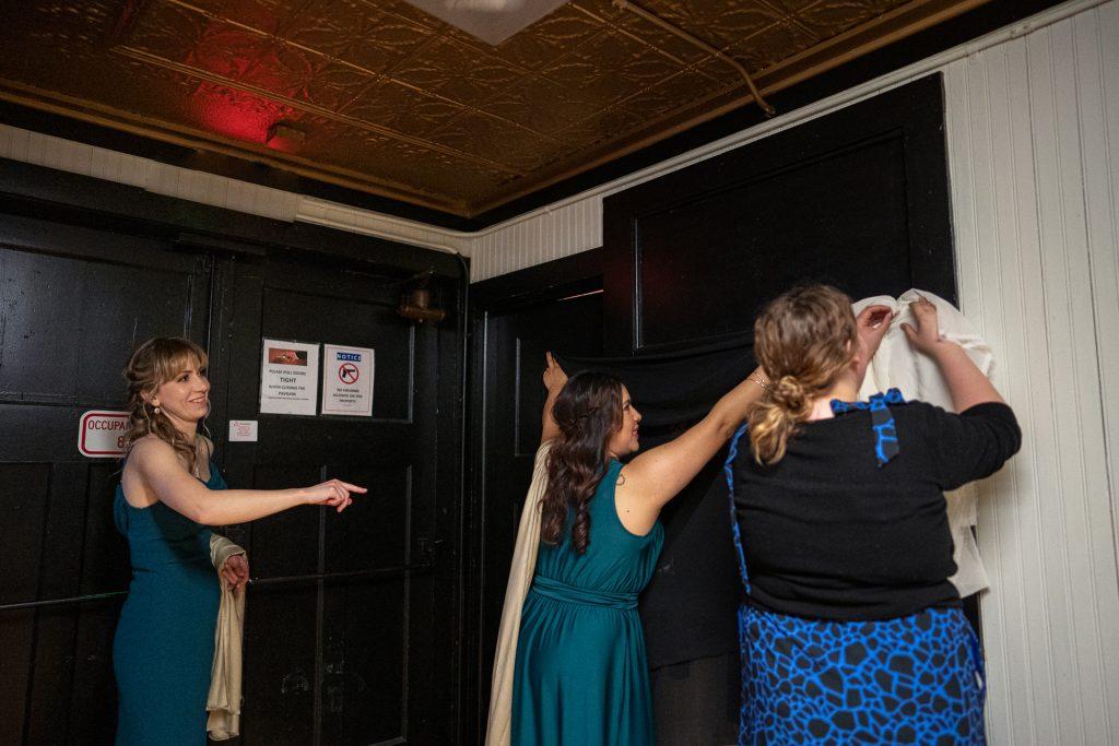 bridesmaids covering brides room windows