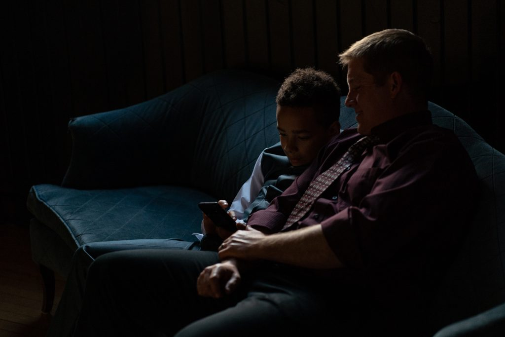 father and son looking at phone