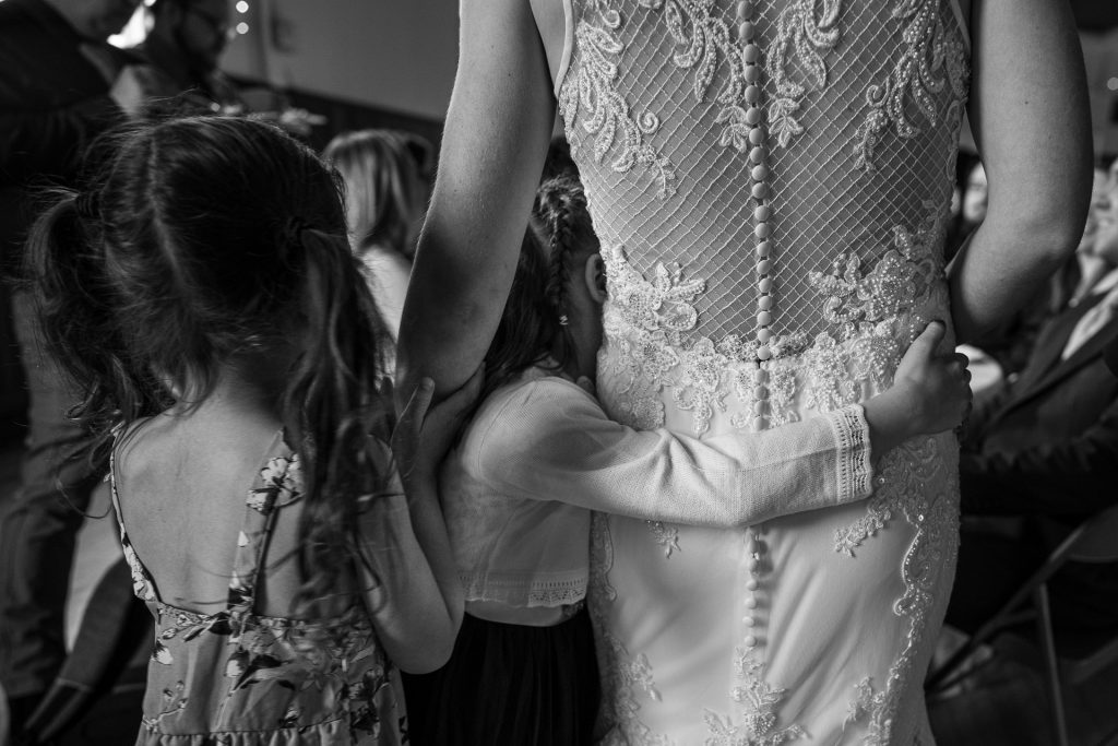 little girls holding on to bride