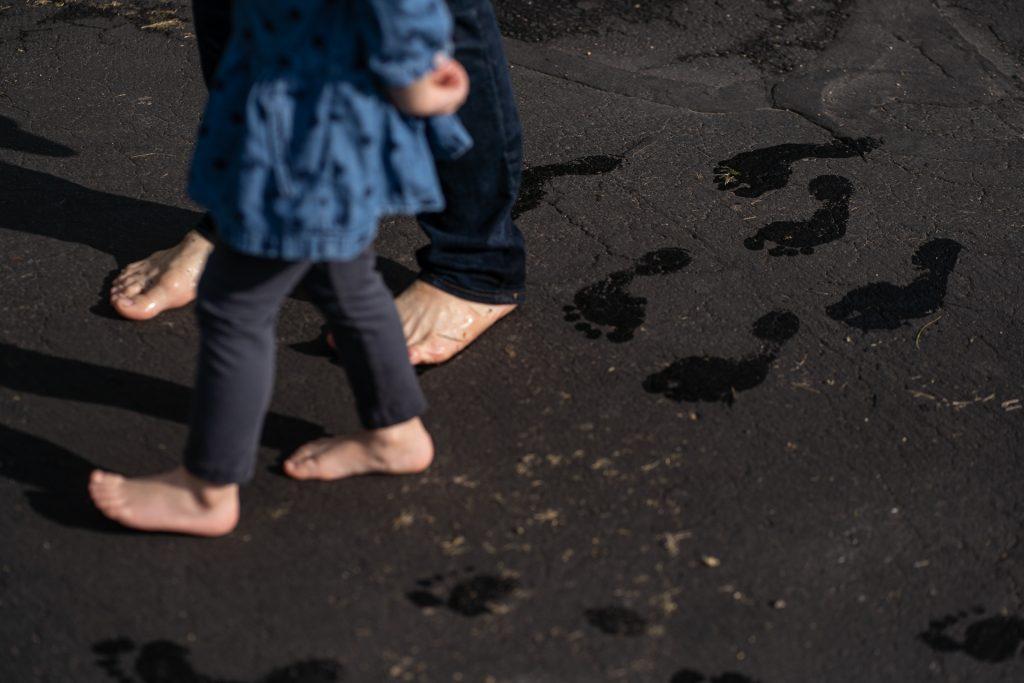 barefoot family leaving wet foot prints on asphalt