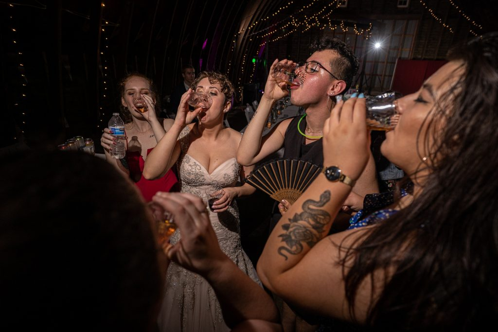 bride drinking a shot with friends