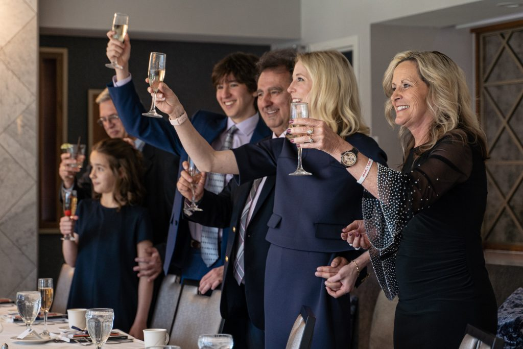 couple and guests raising their glasses