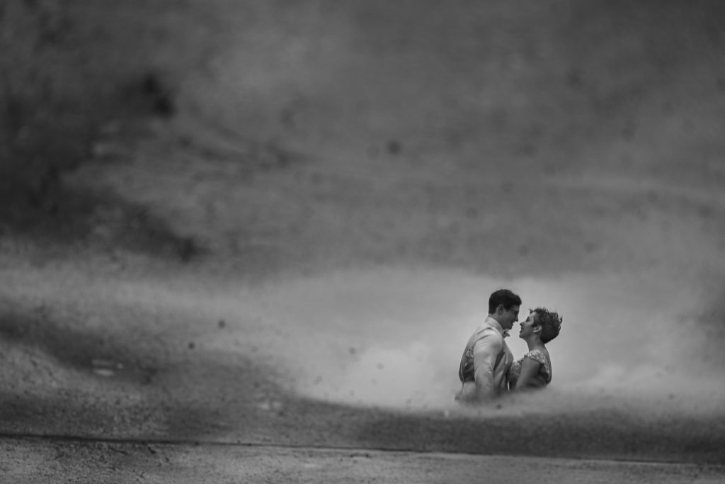 couple through a puddle reflection