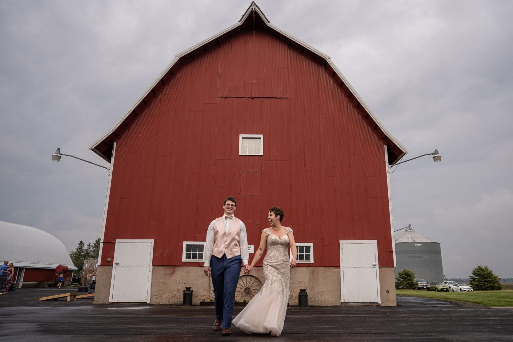 couple walking in front of a red barn
