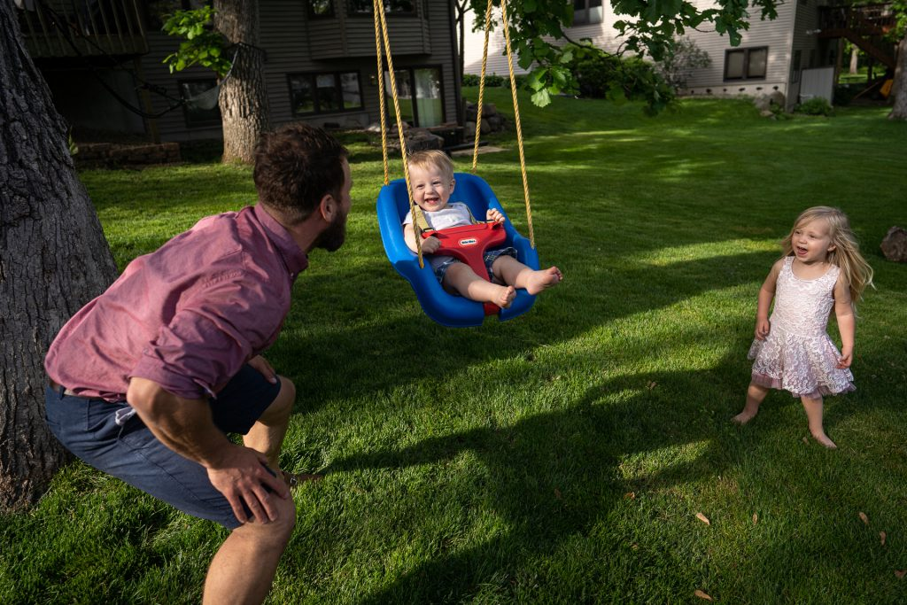 dad blowing son on a swing