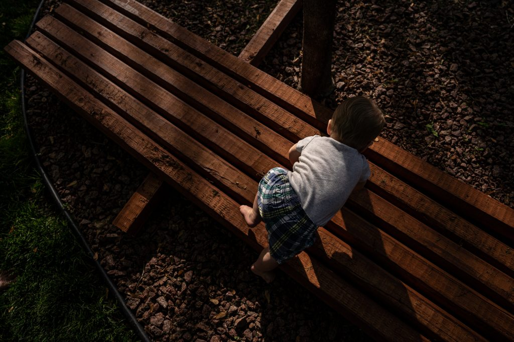 little boy crawling over wood beams