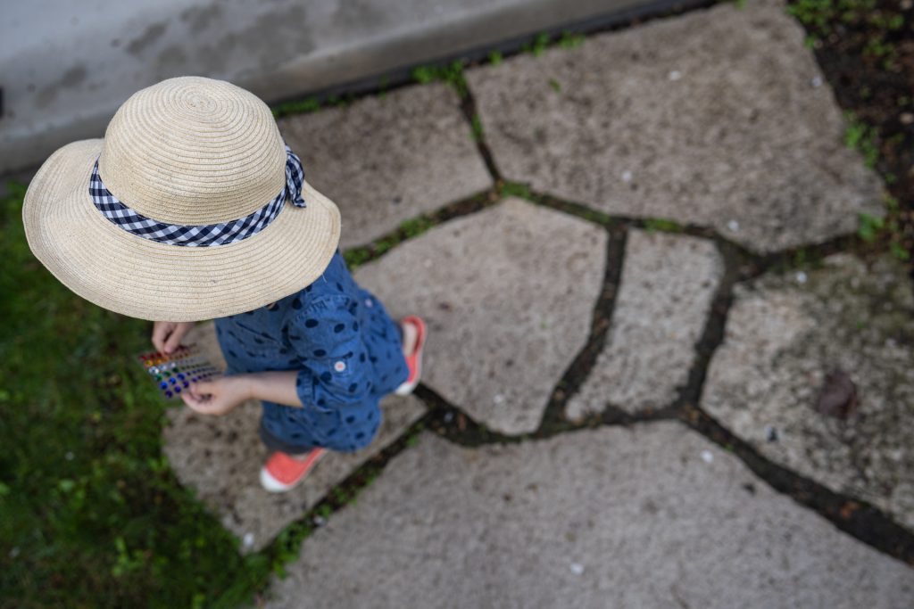 little girl with hat walking over patterned path
