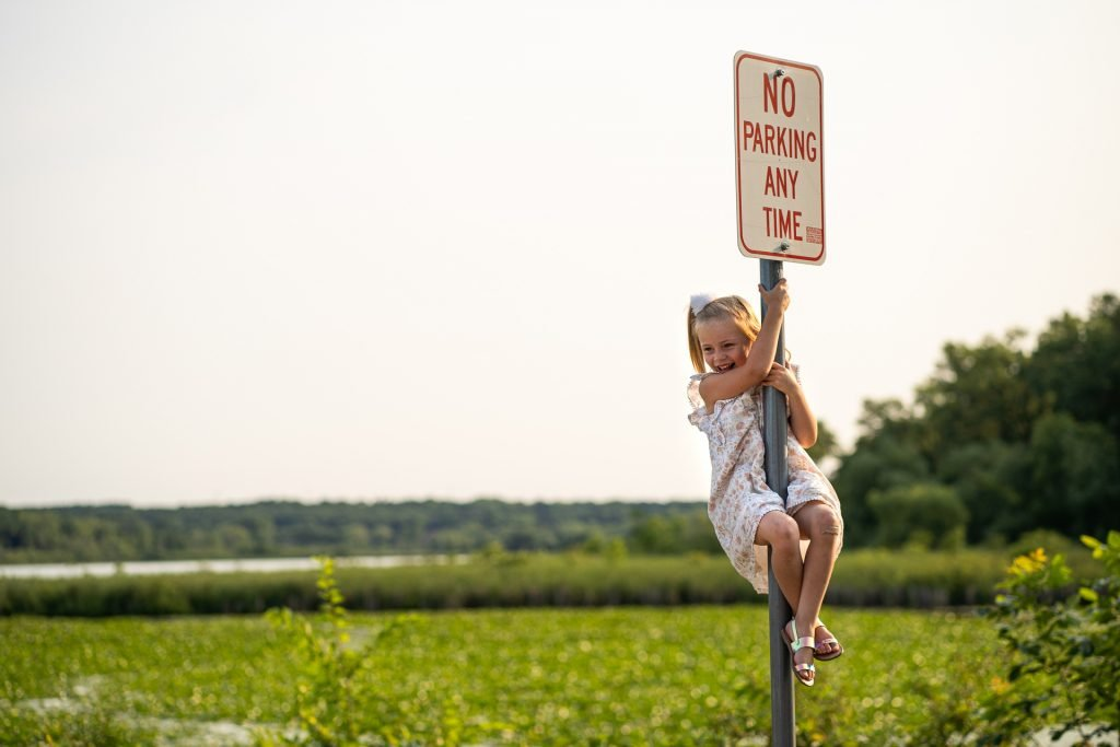 girl hanging on sign post