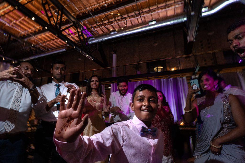 boy dancing with wedding guests