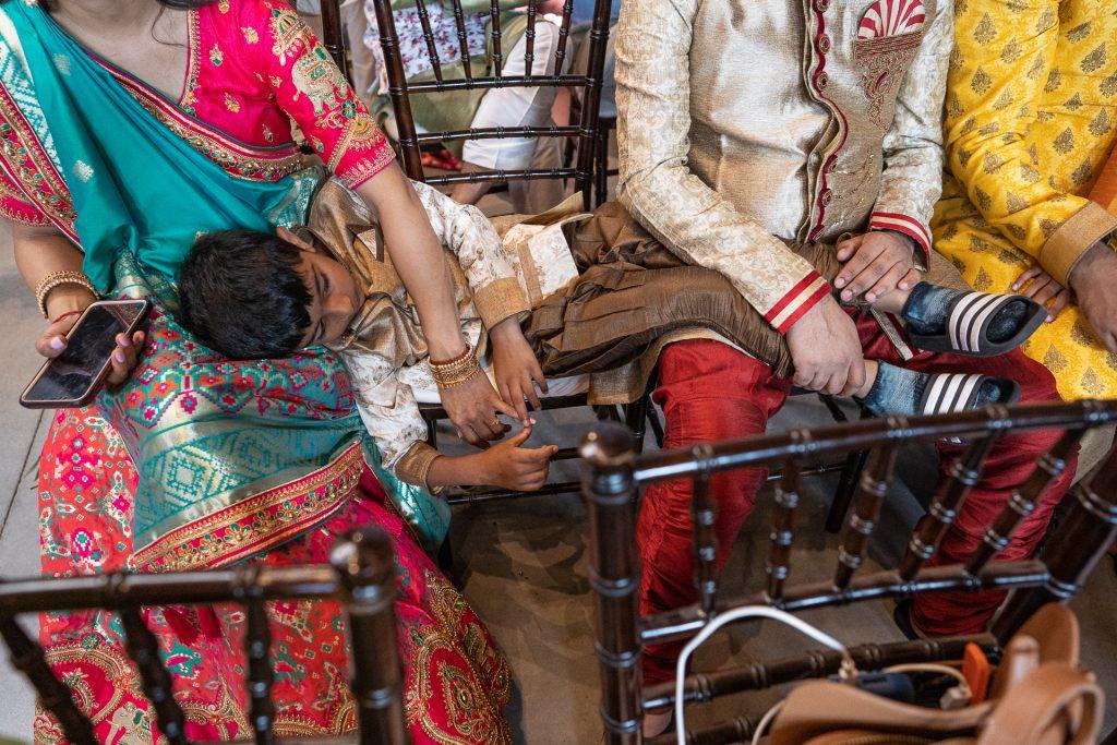 boy sleeping during hindu wedding ceremony